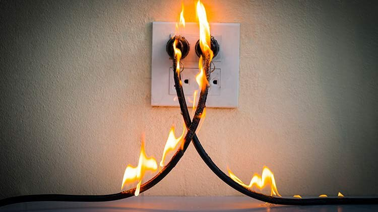 Electrical cords plugged into the wall are on fire due to an arc flash.