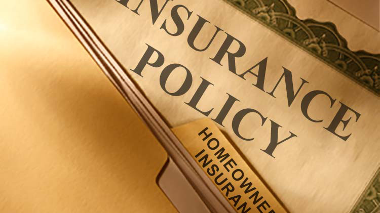 Photo of an insurance policy behind a file folder with Homeowner's Insurance on the tab.