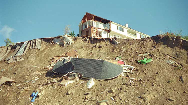 A house damaged by an earthquake sits atop a hill that is covered in debris.