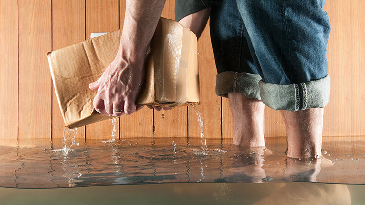Man standing in a flooded basement holding a cardboard box that's dripping.
