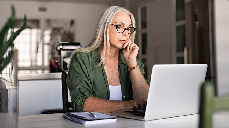 Woman sits in front of laptop, reviewing her estate plan.
