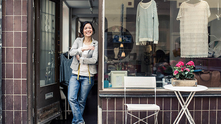 Woman standing at the door of a small business.