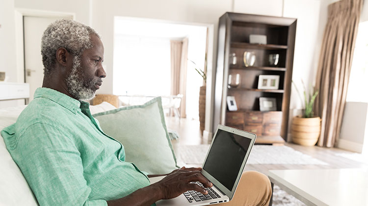 A man uses his laptop to work on his will and estate planning.