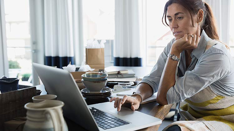 Woman sitting at desk with an open laptop while working from home.