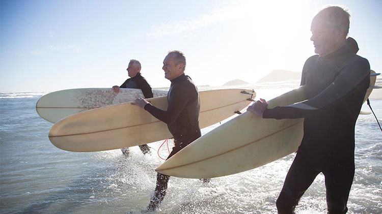 Three retired men are entering the ocean to surf.