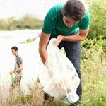 Adolescente recogiendo basura en un río.