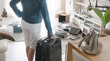 Women walking into apartment with suitcase