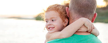 Girl in Dad's arms by rural lake