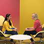 Two women talking in a very colorful room