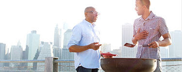 Father and son grilling hamburgers on pier