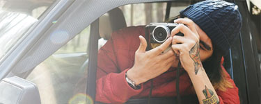 Man in a car with a camera taking a picture