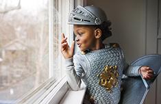 Niño vestido como caballero mirando por la ventana