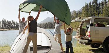 Una familia poniendo la cubierta para la lluvia en su tienda de campaña