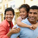 Una familia camina y sonríe mientras la hija va sentada en la espalda de su padre