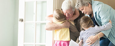 Life Events - Empty Nester - Grandparents hugging grandchildren