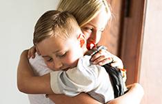 Madre abrazando a su hijo joven