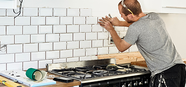 A man setting tile in a new kitchen