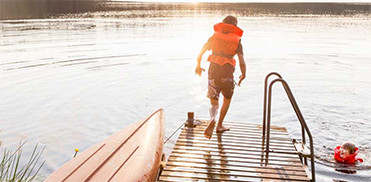 Niños en el agua con chalecos salvavidas