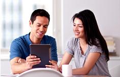 Un hombre y una mujer mirando una tableta sentados alrededor de la mesa durante el desayuno.