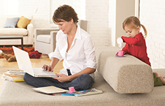 Mom working on computer with daughter playing nearby
