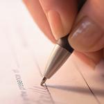 Acercamiento a bolígrafo y cheque donde se está escribiendo