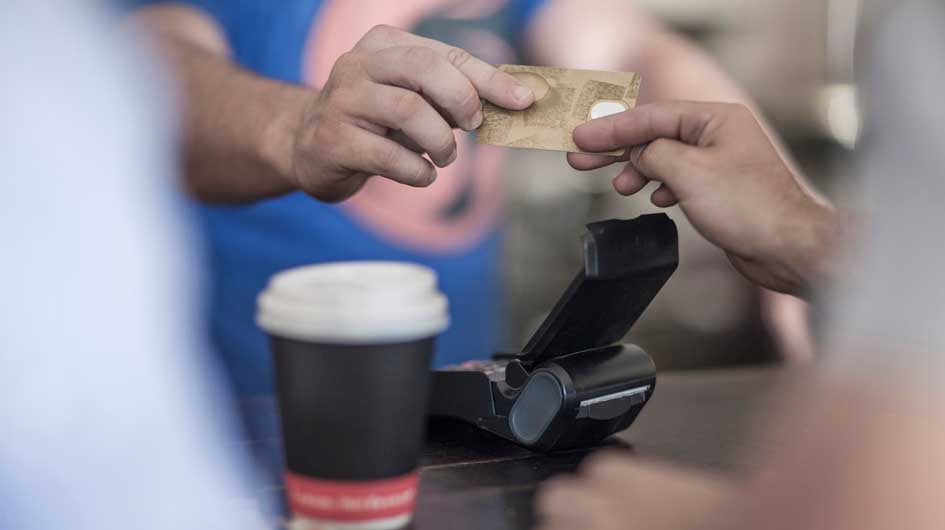 Someone hands over a credit card as a payment for coffee