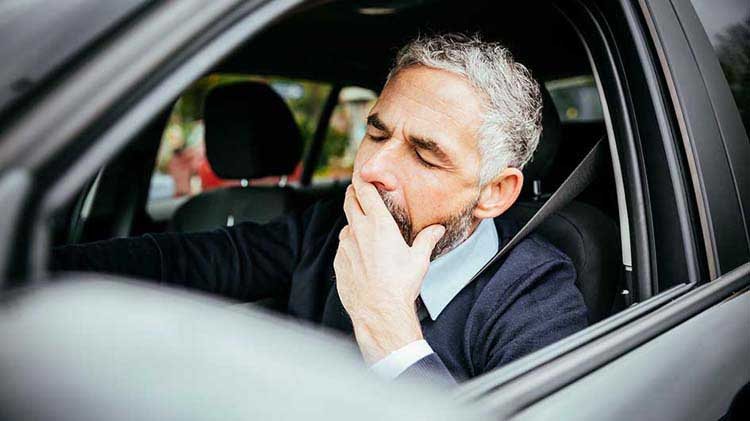 Man yawning at the wheel of a car trying not to fall asleep