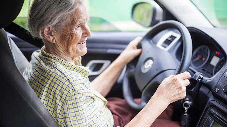 A senior citizen at the wheel of a car