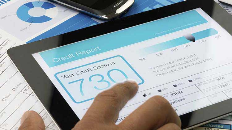 A credit score is displayed on a tablet device