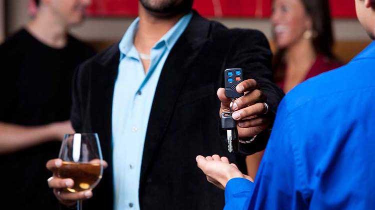 Man with wine glass handing over car keys