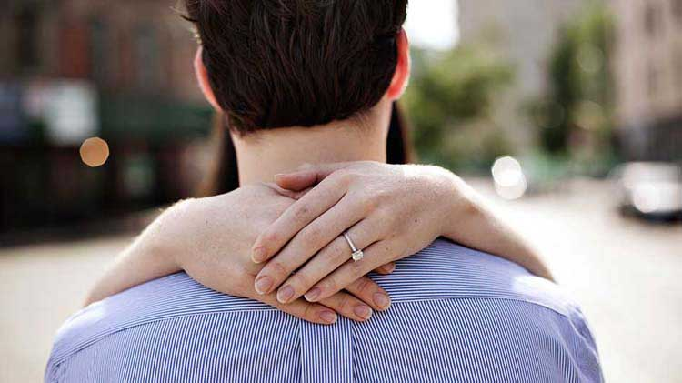 Hands with engagement ring embracing man