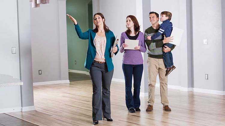 A Realtor showing a home to a young family