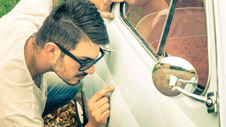 Man looking at paint chip on the side of a car.