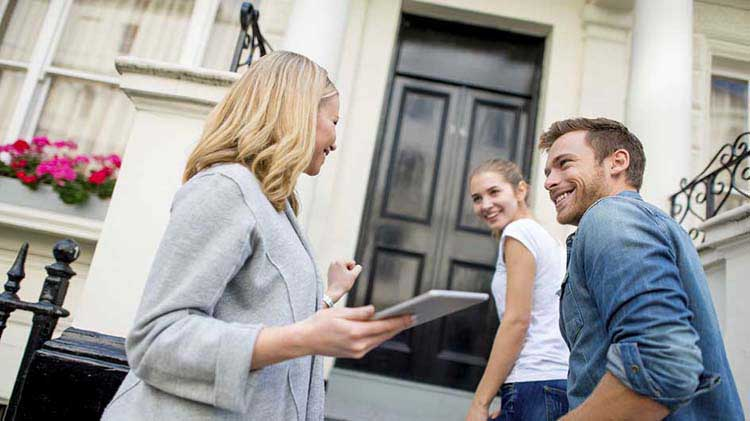 Realtor talking to a young couple on a front porch