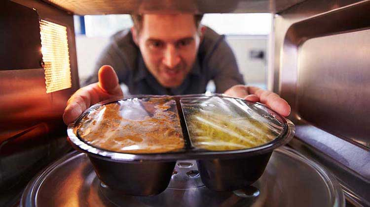 Man putting food in a microwave