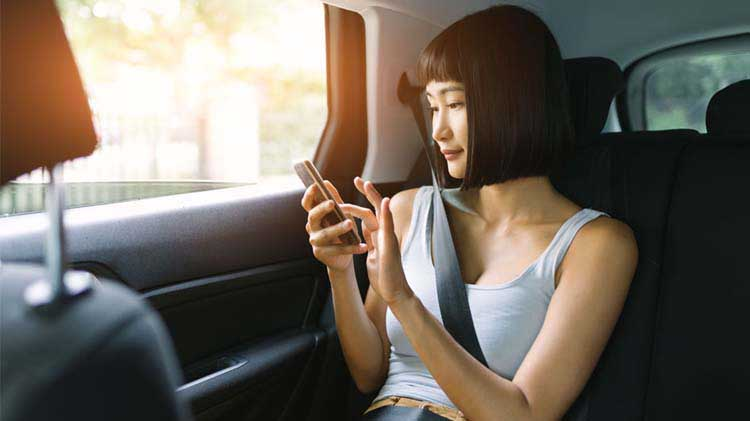 Image of a woman sitting in a car using a cell phone.