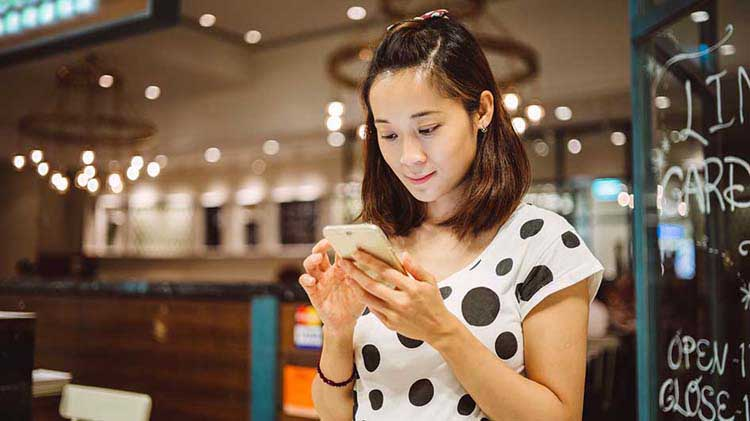 Woman looking at smartphone and accessing her files stored in the cloud