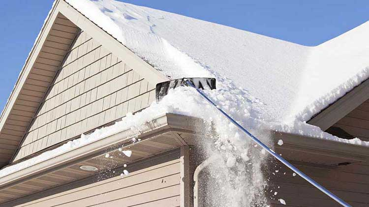 A tool pulls snow down from a roof