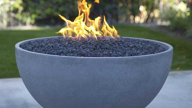 A flaming gas fire pit feature