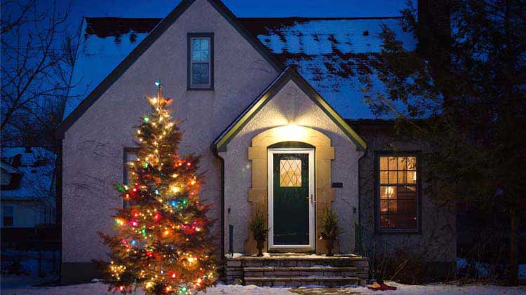 Cozy house in the evening with a lit up Christmas tree outside
