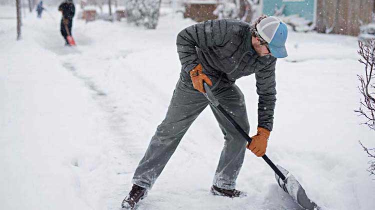 Man shoveling snow to clear a sidewalk