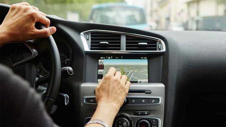 Driver's hand operating an on-board GPS system