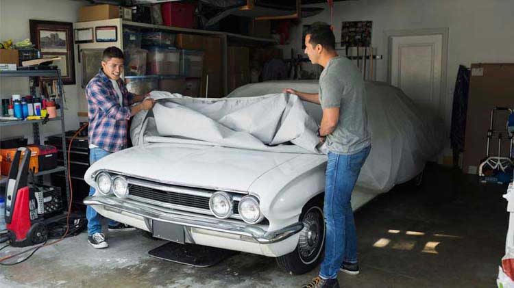 Two men looking at a classic car in a garage