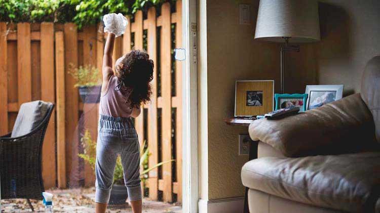 Little girl cleaning a glass sliding door