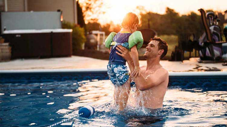 Dad lifting child in swimming pool