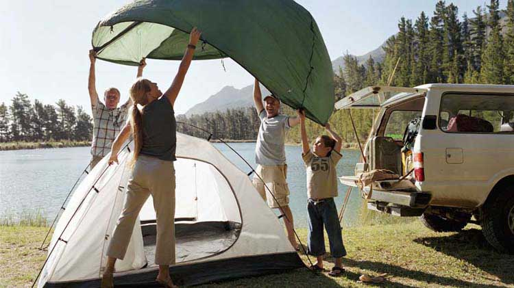 A family putting the rain fly on their tent