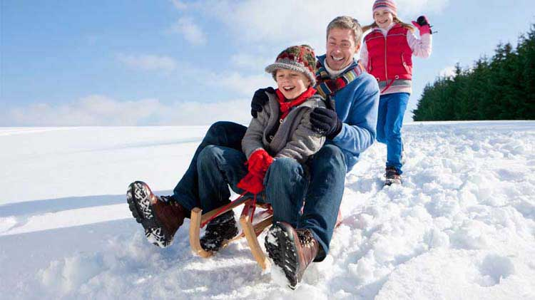 Family sledding in winter