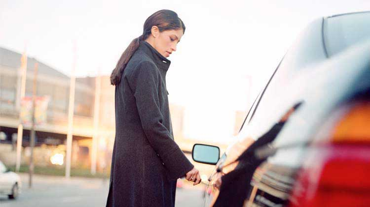 Woman unlocking her car door.