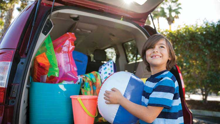 Young boy packing up mini-van with beach toys