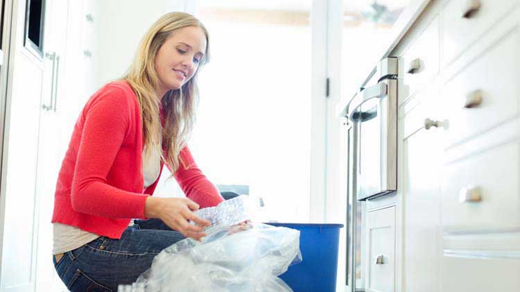 Woman recycling plastic in her kitchen